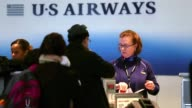 Airways employee help passengers at a checkin counter at Ronald Reagan Washington National Airport on the day before Thanksgiving which is usually...