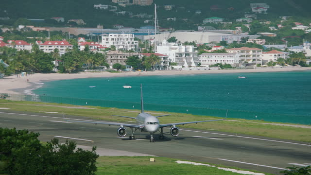 WS TS US Airways plane taxiing in airport, Maho beach in background / St. Maarten