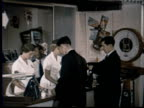 1957 MONTAGE KLM airways sign to ticket agency counter. Agent hands ticket to traveler. Man picks up brochure. British Overseas Airways ticket counter B.O.A.C., PAA Pan American Airways poster / Singapore / AUDIO