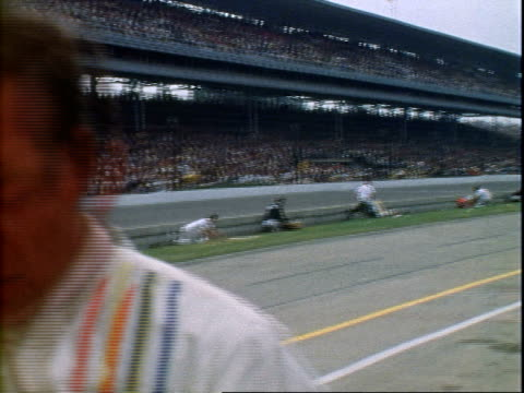 Al Unser Sr racing Colt Ford past packed spectator stands at Indianapolis Motor Speedway / Bobby Unser pulling Eagle Ford into pits for pit stop then...