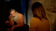 Alan Moore interview Long shot Moore talking to reporter in crypt before door slams shut hiding them from view / Various CUTAWAYS of Alan Moore...