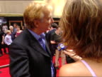DAY Alan Rickman standing on red carpet near Radio City Music Hall talking to press female reporter