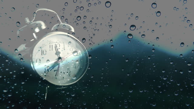 Alarm clock and natural rain drops on mirror background.