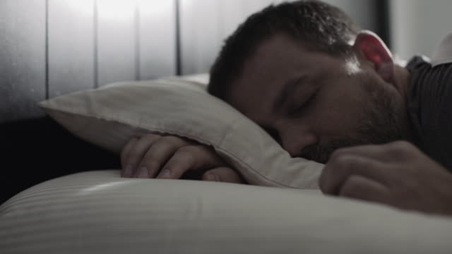 Alarm clock startles sleeping man, he stuffs his head under his pillow