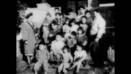 / Alaskan couple adopt 20 children / Alaskan Indian orphans walking in a line / new parents shopping for food / exterior view of large family home /...