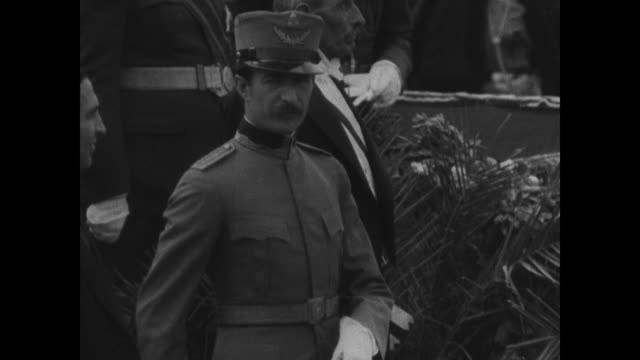 Albania harbor w/ man sitting in wall mountains VS Capitol city of Tirana Bachelor King Zog the I in uniform reviewing saluting troops Albania troops...
