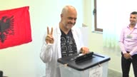 Albanian Prime Minister Edi Rama and his wife Linda Rama cast their ballots for parliamentary election at a polling station in Tirana Albania on June...