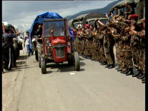 Albanian refugees and vehicles drive past Kosovan Liberation Army guard of honour lined up to welcome them back to Kosovo 21 Jun 99