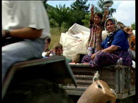 Albanian refugees return to Kosovan villages in trucks giving victory signs and waving at camera 21 Jun 99