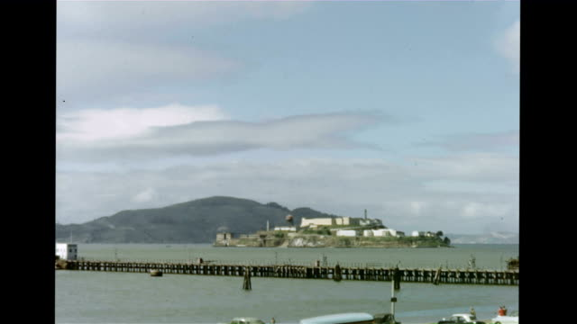 / Alcatraz Island from the shore seen through the trees / closer view of island with pier in front View of Alcatraz Island on January 01 1960 in San...