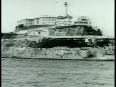 ALCATRAZ Alcatraz maximum security Federal Prison w/ San Francisco Bay waters FG Several prisoners turning toward cells walking into cells guard...