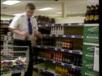 Five brands scrapped LIB ENGLAND Lancs Salford Coop supermarket Man removing bottles of alcopops from supermarket shelf and placing them in trolley