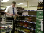 Five brands scrapped LIB Lancs Salford Coop supermarket Man removing bottles of alcopops from supermarket shelf and placing them in trolley