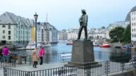 Alesund Norway cruise Hurtigruten downtown near pier Sailor's Statue with passengers enjoying the scewnic water homes in city