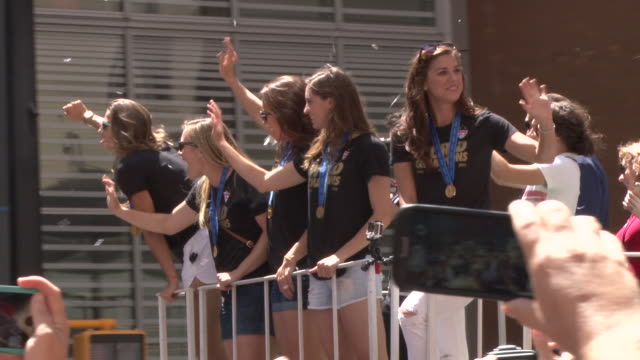 Alex Morgan along with other members of the US Women's Soccer Team wave to fans at the Ticker Tape Parade in Downtown Manhattan celebrating their...