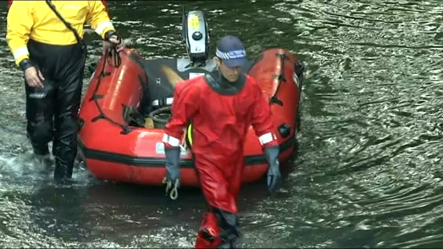 Police investigation to be reviewed London EXT Police search officers along in River Brent with dog on inflatable boat Police officer using strimmer...