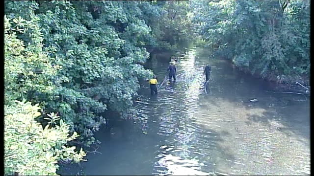 Police search River Brent ENGLAND London Ealing EXT Various shots of police officers in wetsuits searching banks and shallows of River Brent