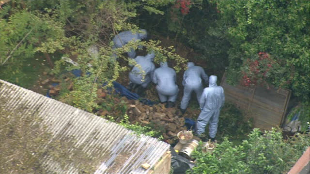 Body found in River Brent AERIAL police forensic officers searching through grass area in garden behind building with corrugated iron roof forensic...