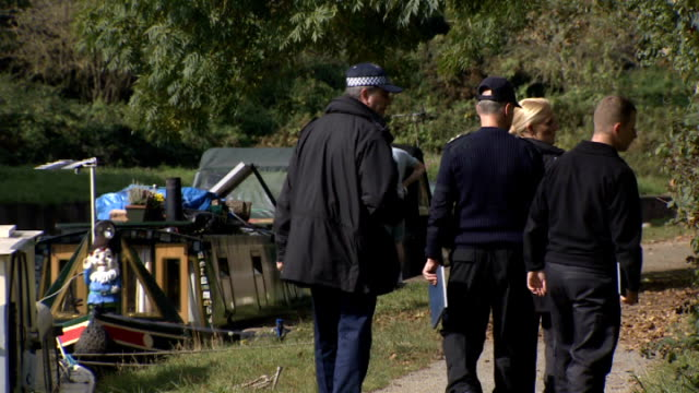 Body found in River Brent Purple flower on plant 'Sweet dreams' canal boat Man along next to boats moored in water Vox pops EXT Police officers along...