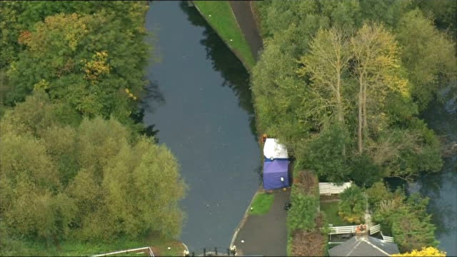 Police hunting suspect Arnis Zalkalns find body R01101407 Police forensics tents erected on the bank of the River Brent