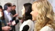 Alison Pill in FG and Olivia Munn BG talking to reporters along the red carpet at Saban Theater