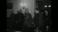 Allied and Soviet officers entering building where surrender will be signed US Soviet and British flags over entrance / officers seated around long...