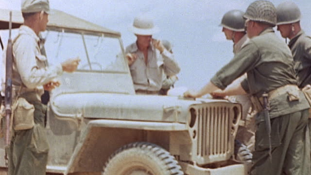 Allied command staff conferring over map spread on Jeep's hood parked by train tracks and looming mountain / Saipan Mariana Islands
