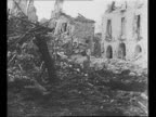 Allied soldiers approach as they walk single file up slope during World War II Battle of Monte Cassino / pan ruins of town of Cassino / US soldiers...