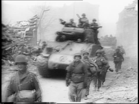 Allied troops march through field / tanks and military march through town / cow walks beside them / troops place missiles in Rocket Tank / missiles...