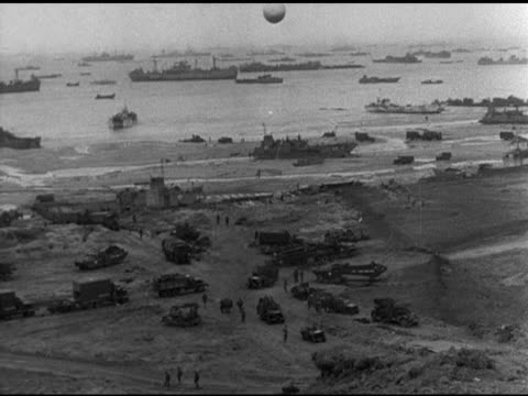 Allied troops securing cleaning up Omaha Beach ships in English Cannel BG MS US Soldiers riding Sherman tank Allied Tank armored vehicles on road V...