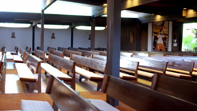 TS PAN along rows of pews stocked with bibles and prayer materials and rack of burning votive candles inside catholic church