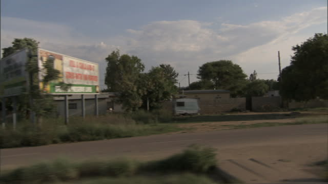 Along street in Gaborone passing various advertisement billboards streets trees Rural countryside