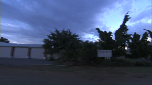 Along street in Gaborone passing various factories plants warehouses South Africa rural countryside