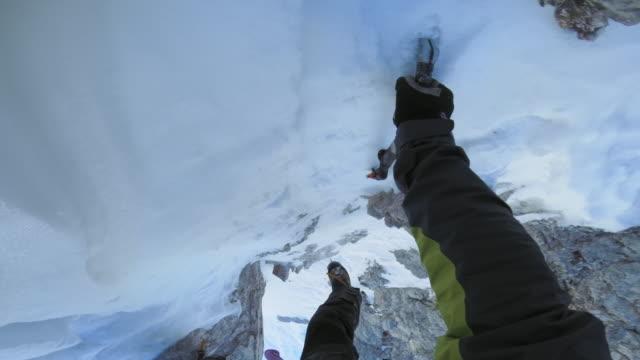 POV Alpinist climbing down a steep snowy mountain top