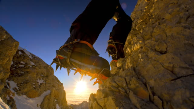 Alpinist climbing the mountain peak in sunshine