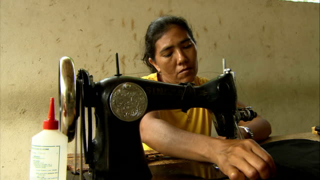 Tapajos River / general views of Maguari Community INT Woman using sewing machine to manufacture bag from latex sheet / close up of sewing machine /...