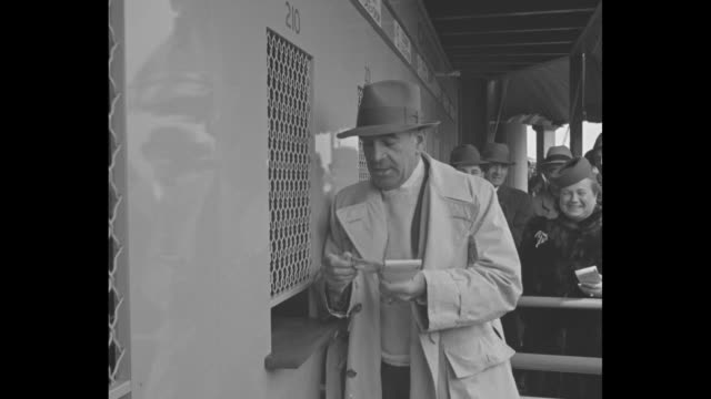 US Ambassador to Canada James H R Cromwell wearing fedora sits in viewing seats at Jamaica Racetrack in Queens New York City he chats and laughs /...