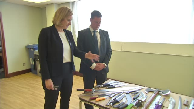 Amber Rudd launches new measures to tackle knife crime ENGLAND London INT Close Shots of knives on table / Amber Rudd MP is shown a collection of...