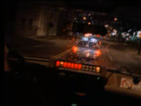 Ambulance point of view behind police car at night