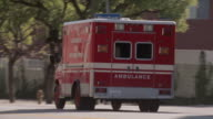 TS Ambulance speeding down a city street / Los Angeles, California, United States