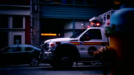 Ambulance standing in front of building entance with siren blinking