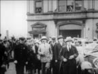 Amelia Earhart holding flowers walking with men to car / NYC / newsreel