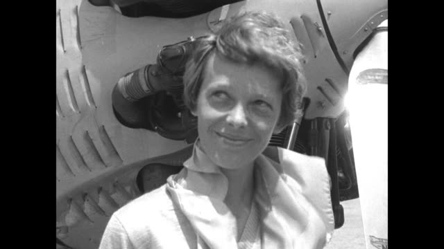 CU Amelia Earhart standing next to airplane wearing blouse with ruffled collar / CU Marvel Crosson in flight helmet and goggles standing near wing of...