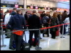 American Express report on air fares ITN London Heathrow Airport Long queue of people at airport checkin area MS People along in queue TRACK past...