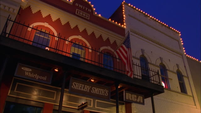 American flag flying from balcony above illuminated store front at night, Canton, Mississippi Available in HD.