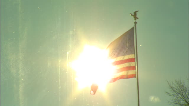 MS American flag flying on top of pole eagle topper sun visible through 'Old Glory' quick ZO reveals top of bare braches weather vane on roof of...