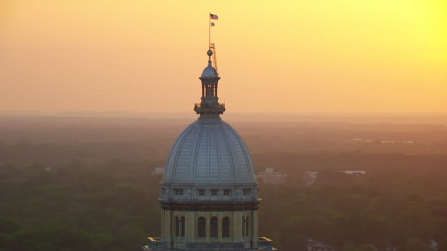 WS DS AERIAL POV American flag waving on top of Illinois State Capitol building at sunset / Springfield, Illinois, United States