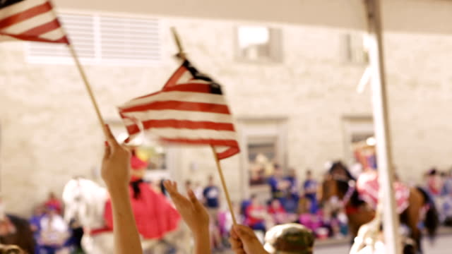 American flags being waved by family as they attend Independence Day parade