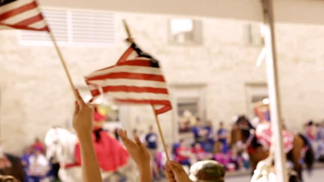 Bandiere americane essere ha salutato da una famiglia che frequentano Independence Day parade