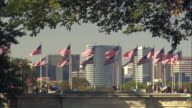 WS American Flags flapping on wind, skyscrapers in background / Rosslyn, Virginia, USA